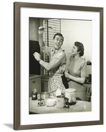 Young Cheerful Couple in Kitchen, Man in Apron-George Marks-Framed Photographic Print