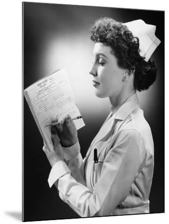 Young Nurse Writing on File in Studio-George Marks-Mounted Photographic Print