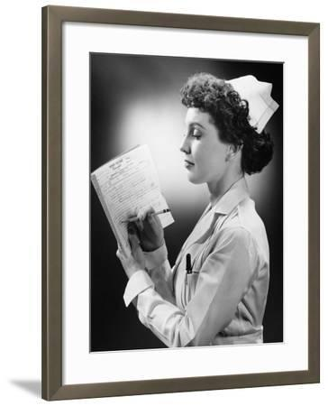 Young Nurse Writing on File in Studio-George Marks-Framed Photographic Print