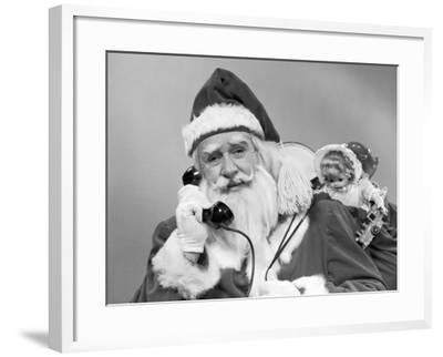 Santa Claus on the Telephone With His Sack of Toys on His Back-H^ Armstrong Roberts-Framed Photographic Print