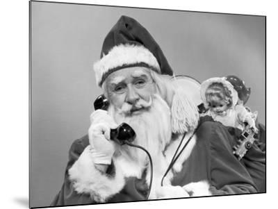Santa Claus on the Telephone With His Sack of Toys on His Back-H^ Armstrong Roberts-Mounted Photographic Print