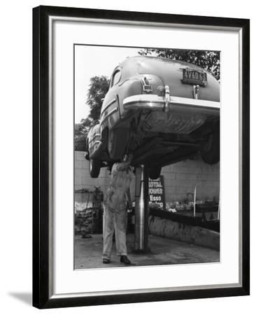 Mechanic Working on Underside of Car-George Marks-Framed Photographic Print