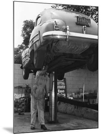 Mechanic Working on Underside of Car-George Marks-Mounted Photographic Print
