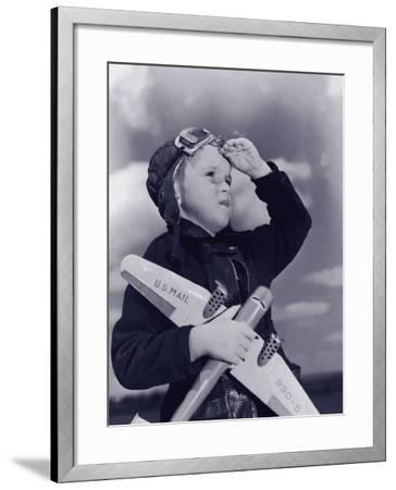 Boy (8-10) Wearing Flying Cap and Goggles Holding Toy Plane--Framed Photographic Print