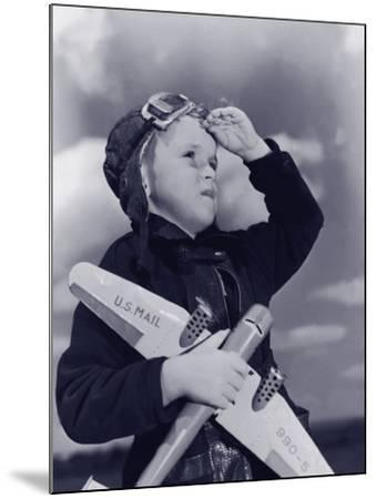 Boy (8-10) Wearing Flying Cap and Goggles Holding Toy Plane--Mounted Photographic Print