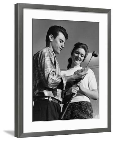 Man Showing Golf Club To Woman--Framed Photographic Print