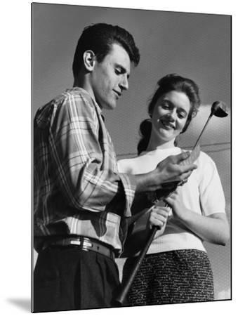 Man Showing Golf Club To Woman--Mounted Photographic Print