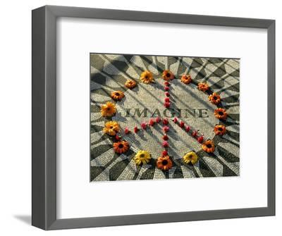 A Makeshift Peace Sign of Flowers Lies on Top John Lennon's Strawberry Fields Memorial--Framed Photographic Print