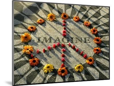A Makeshift Peace Sign of Flowers Lies on Top John Lennon's Strawberry Fields Memorial--Mounted Photographic Print
