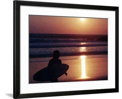 A Surfer is Silhouetted by the Setting Sun as He Leaves the Pacific Ocean on Venice Beach--Framed Photographic Print