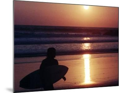 A Surfer is Silhouetted by the Setting Sun as He Leaves the Pacific Ocean on Venice Beach--Mounted Photographic Print
