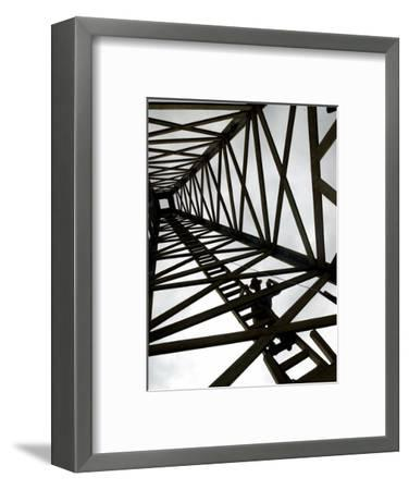 A Reenactor is Silhouetted Inside a Replica of the Spindletop Oil Derrick--Framed Photographic Print