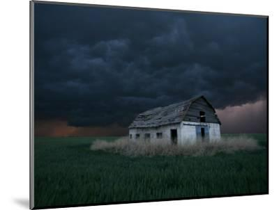 Old Barn Stands in a Wheat Field as a Thunderstorm Passes in the Distance Near Ogallah, Kansas--Mounted Photographic Print