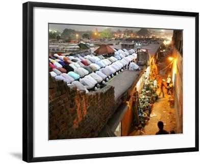 Indian Muslims During Friday Evening Prayers on the Rooftop of a Building over an Auto Parts Market--Framed Photographic Print