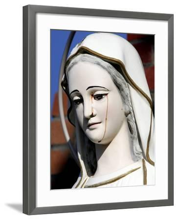 Red Stains are Seen Running from the Left Eye of a Statue of the Virgin Mary--Framed Photographic Print