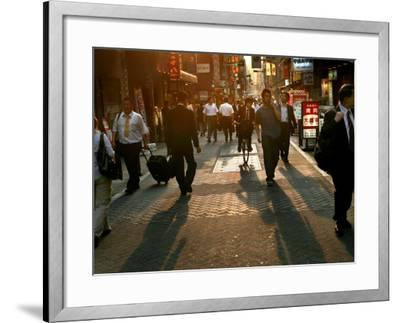 Japanese Commuters Walk Through a Tokyo Street on Their Way to the Train Stations-David Guttenfelder-Framed Photographic Print