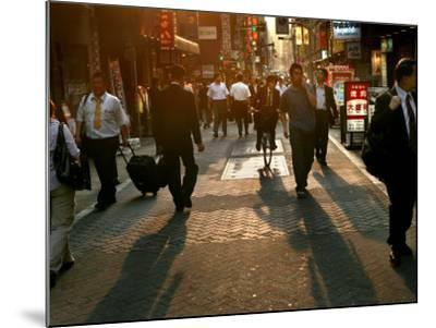 Japanese Commuters Walk Through a Tokyo Street on Their Way to the Train Stations-David Guttenfelder-Mounted Photographic Print