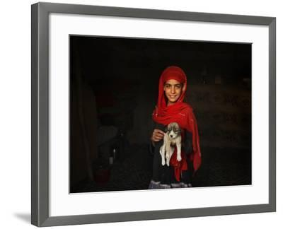 Girl Holds a Puppy as the Sun Sets over Kabul's Impoverished Teppe Maranjan Neighborhood--Framed Photographic Print