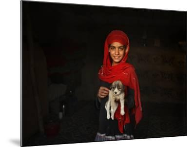 Girl Holds a Puppy as the Sun Sets over Kabul's Impoverished Teppe Maranjan Neighborhood--Mounted Photographic Print