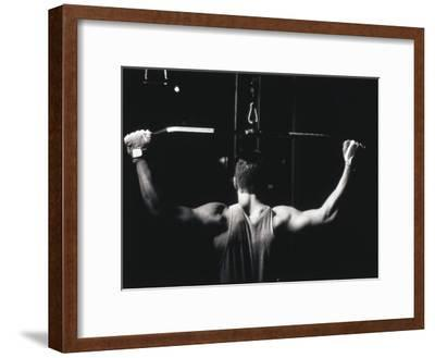 Rear View of a Young Man Exercise on a Lateral Pull-Down Weight Machine--Framed Photographic Print