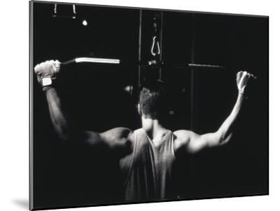 Rear View of a Young Man Exercise on a Lateral Pull-Down Weight Machine--Mounted Photographic Print