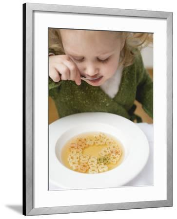 Small Girl Eating Soup with Teddy Bear Pasta--Framed Photographic Print