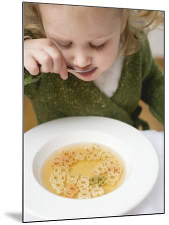 Small Girl Eating Soup with Teddy Bear Pasta--Mounted Photographic Print