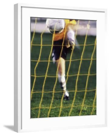 Soccer Player Kicking a Soccer Ball--Framed Photographic Print