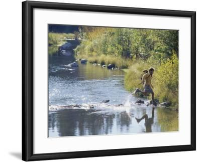 Side Profile of a View of a Young Man Running Across a River--Framed Photographic Print