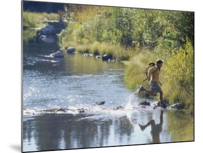 Side Profile of a View of a Young Man Running Across a River--Mounted Photographic Print