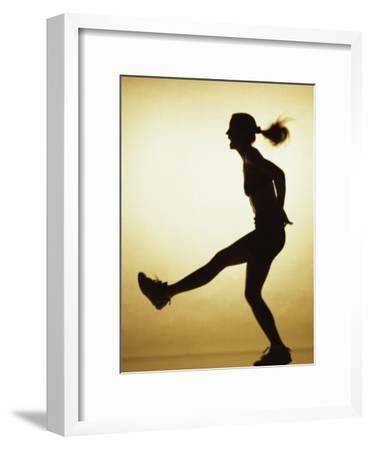 Silhouette of a Young Woman Exercising--Framed Photographic Print