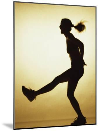 Silhouette of a Young Woman Exercising--Mounted Photographic Print