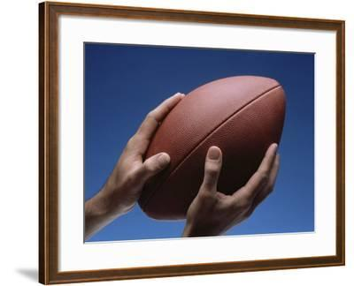 Hands Holding Football with Blue Background--Framed Photographic Print
