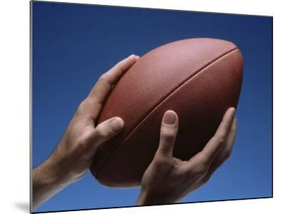 Hands Holding Football with Blue Background--Mounted Photographic Print