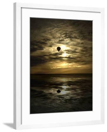 Silhouette of a Hot Air Balloon Over Water--Framed Photographic Print