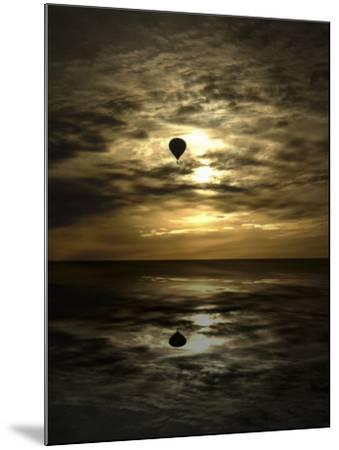 Silhouette of a Hot Air Balloon Over Water--Mounted Photographic Print