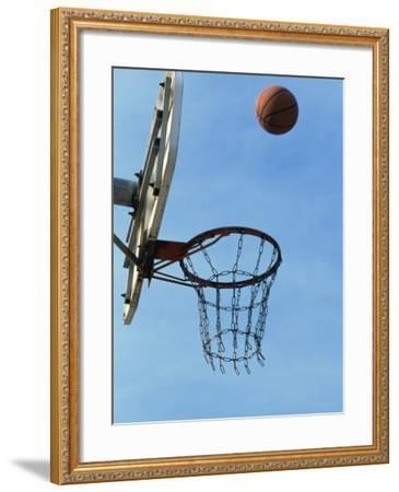 Low Angle View of a Basketball Bouncing Off The Hoop--Framed Photographic Print