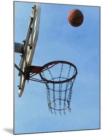Low Angle View of a Basketball Bouncing Off The Hoop--Mounted Photographic Print