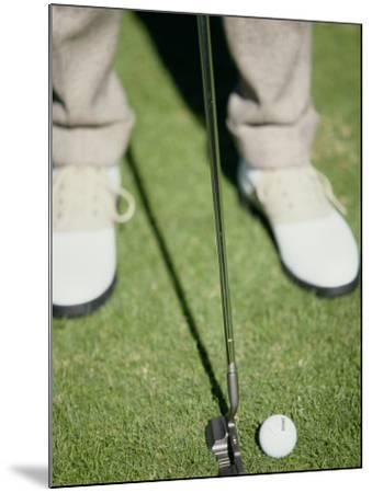Low Section View of a Man Putting a Golf Ball--Mounted Photographic Print