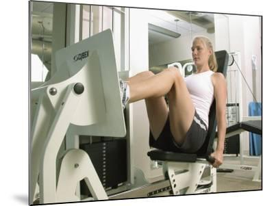 Young Woman Exercising on a Machine in a Gym--Mounted Photographic Print