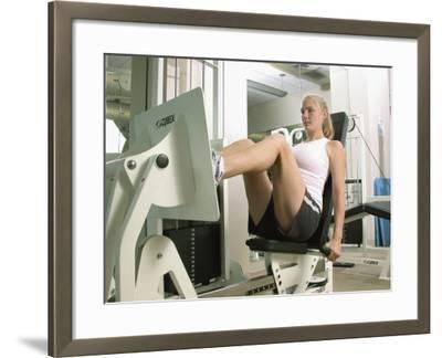 Young Woman Exercising on a Machine in a Gym--Framed Photographic Print