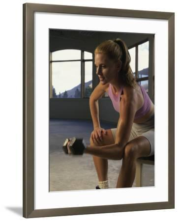 Young Woman Sitting on a Bench Lifting a Dumbbell--Framed Photographic Print