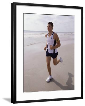 Young Man Jogging on the Beach--Framed Photographic Print