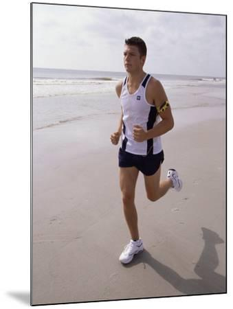 Young Man Jogging on the Beach--Mounted Photographic Print