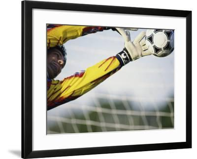 Goalie Attempting to Stop a Soccer Ball--Framed Photographic Print