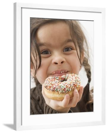 Girl Holding a Doughnut with Sprinkles, Partly Eaten--Framed Photographic Print