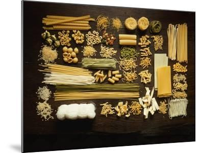 Many Different Types of Pasta on Dark Wooden Background-Walter Cimbal-Mounted Photographic Print