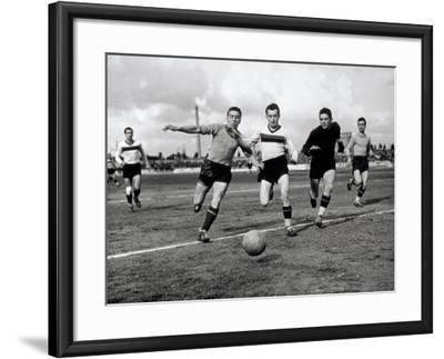 Soccer Players Running after the Ball During a Game-A^ Villani-Framed Photographic Print