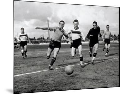 Soccer Players Running after the Ball During a Game-A^ Villani-Mounted Photographic Print