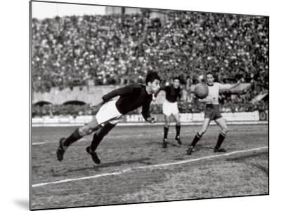 Soccer Player Shown While Heading the Ball-A^ Villani-Mounted Photographic Print